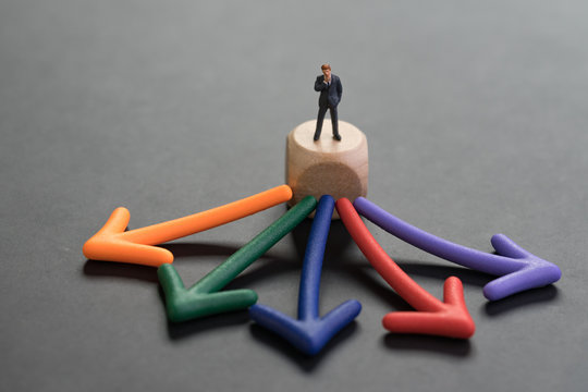 Career or opportunity choices for work, business decision concept, miniature businessman or salary man standing and thinking on wooden cube with multi direction color arrow pointing out on blackboard