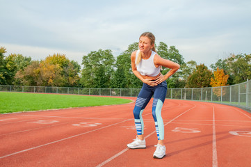 Woman on running track has side cramps during workout