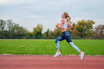 Athletic woman running on athletics race track.