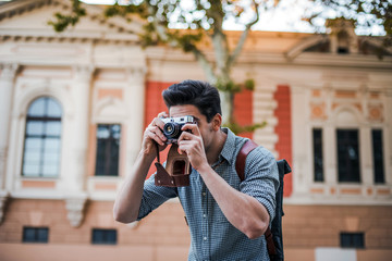 Close up shot of young attractive handsome man tourist with backpack taking photos on vintage camera in old city center