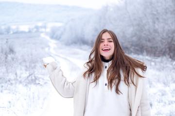 Happy winter woman on on snowy background. Outdoors. Joyful Beauty young woman Having Fun in Winter Park. Winter woman snow. Winter woman clothes.