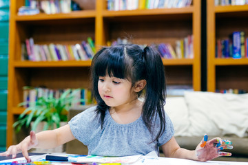 Cute little girl painting a picture at home