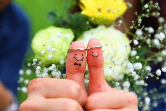 親指に結婚指輪をして顔を描いた写真(中心)