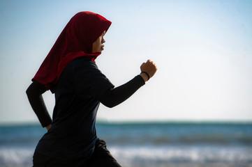 Woman wearingMuslimahSportswear running along sea, Malaysia