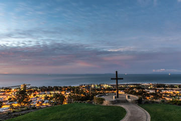 Christian wooden cross stands tall over city lights of Ventura along the Pacific Ocean coast as dawn begins to light the cloudy sky.
