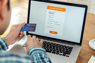 Young man filling credit card information making payment online