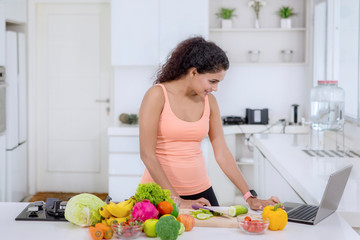Curly hair woman looking at recipes on a laptop
