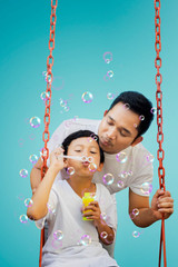 Father blowing soap bubbles with his son