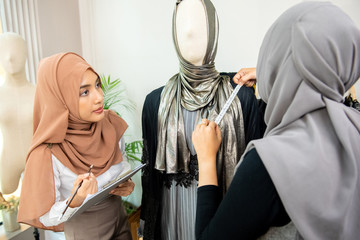 Muslim woman designer working with colleague measuring size of the dress