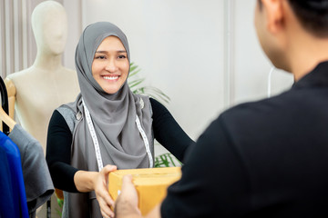 Muslim woman designer receiving parcel box from delivery man
