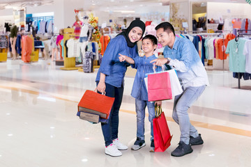 Happy little boy with his parents in mall