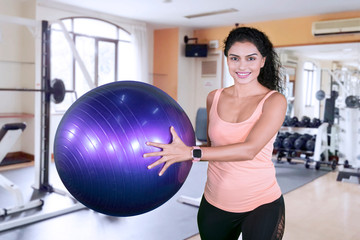 Happy sporty woman holding a yoga ball
