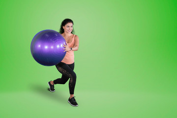 Indian woman exercises with a yoga ball on studio