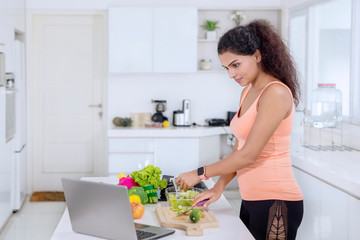 Indian woman looking at recipes on a laptop