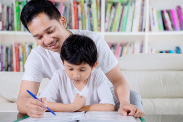 Little boy guided by his father to read a book