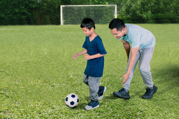 Little boy playing football with his father
