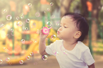 Little girl blowing soap bubbles in the playground