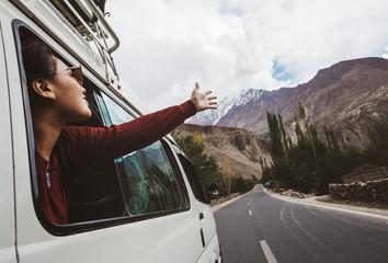 Zelfklevend Fotobehang Diepbruine Young woman enjoying traveling by car across mountain landscape
