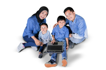 Two children using a laptop with their parents