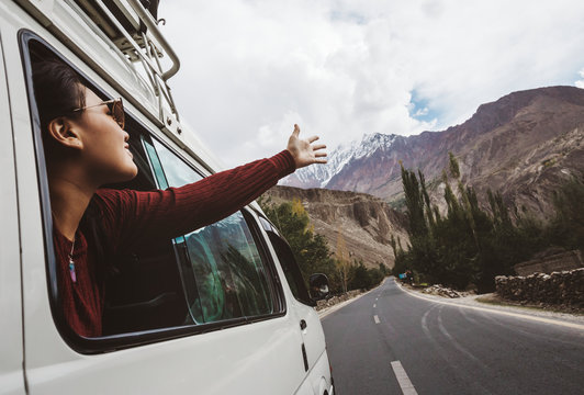 Young woman enjoying traveling by car across mountain landscape