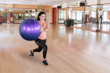 Young Indian woman exercises with a yoga ball