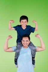 Young man piggybacking his son on studio