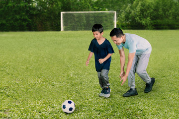 Young man playing football with his son