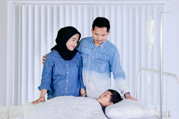 Young parents visiting their sick son in the clinic