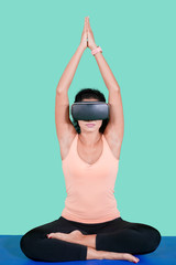 Young woman meditates with virtual reality goggles