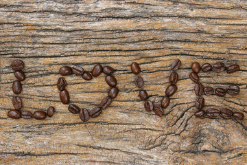 coffee beans used to spell love text on wood background..