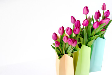 Fresh bright bouquet of pink tulip in paper bags. Beautiful greeting card. Spring holidas concept.
