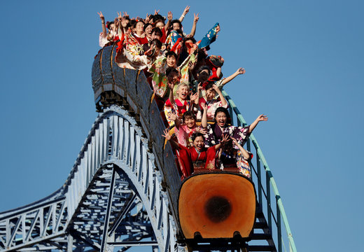 Japanese women wearing kimonos ride a roller coaster during their Coming of Age Day celebration ceremony at Toshimaen amusement park in Tokyo