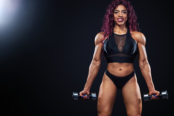 First egyptian and muslim woman athlete with dumbbells makes fitness exercising on black background with lights.