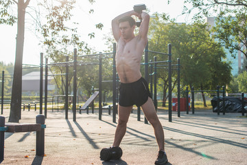 Muscular male athlete with arms raised doing lifting exercises dumbbells.