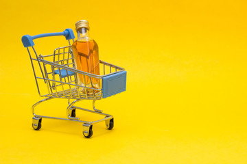 Small bottle with alcohol in a shopping basket, close-up, copy space, orange background, consumerism