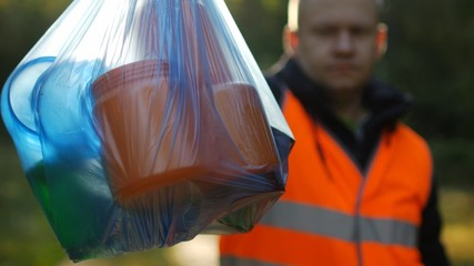 A man in a signal orange vest holds a package with garbage on the background of nature, forest, close-up, garbage collection, a janitor, volunteer, rubbish
