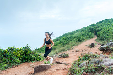 Sporty young woman in black sportswear trail running on mountain nature path. Fit girl jogging downhill rocky track.