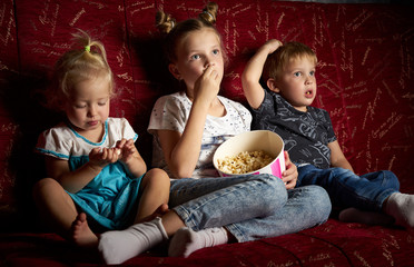 Children's movies: Three children watch movies at home on a big red sofa in the dark and eat popcorn.