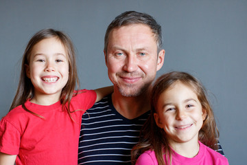 family photo dad with two young daughters