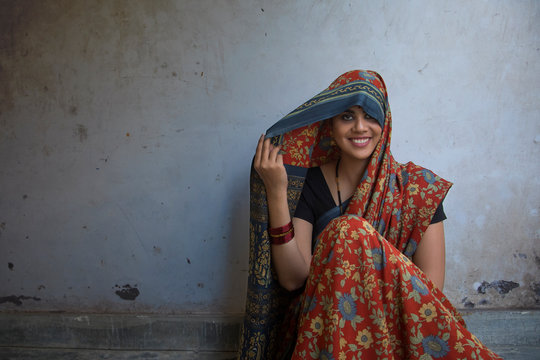 Closeup of a beautiful smiling woman sitting on the floor covering her head with saree.