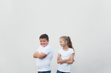 beautiful happy smiling young fat boy and thin little girl in white shirt on bright background with copy space