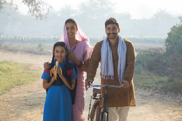 Happy rural family consisting of man, woman and a school going girl walking on pathway in a village.
