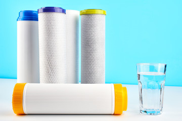 Water filters. Carbon cartridges and a glass on a white blue background. Household filtration system.