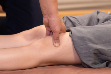 Professional therapist giving traditional thai leg and body massage to a woman in spa