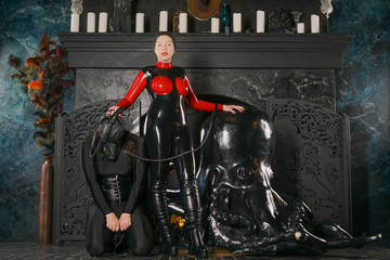 evil strong mistress with black hair wearing fetish latex catsuit and playing with her dog slave in leather mask on dark gothic background