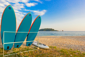 Surfboards are on the rack. Off the coast of the sea with an island in the background