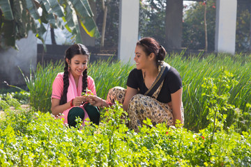 Rural woman working in agriculture field along with her daughter on a sunny day.