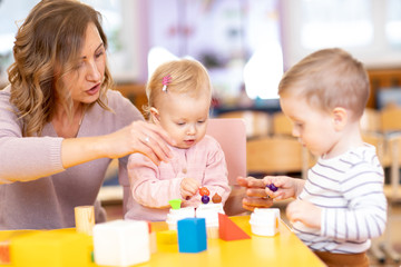 Nursery teacher with children boy and girl learn color and size while playing together. Early education concept.