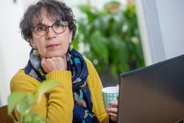 portrait of beautiful brunette mature woman with a laptop at home
