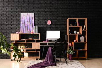 Stylish workplace with modern computer near dark brick wall